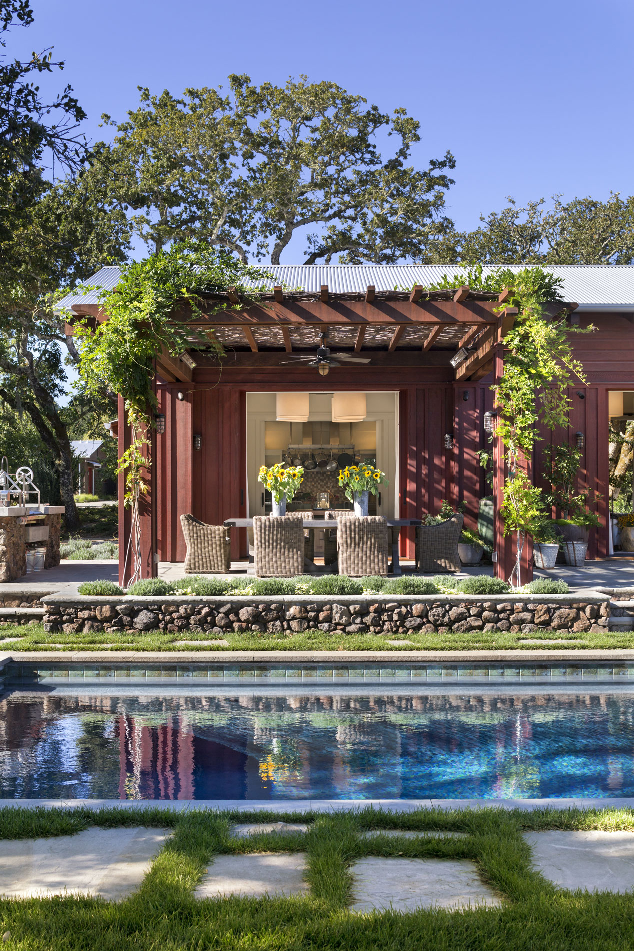View of the wisteria-covered dining pergola across the pool. (Photo credit: Peter Aaron/OTTO for Robert A.M. Stern Architects)
