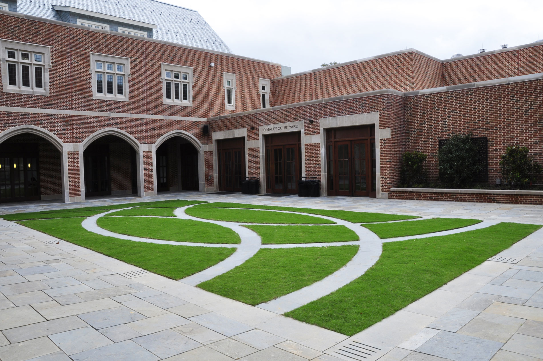 View of the courtyard showing lawn panel with bluestone bands, seat wall, and Camellias espaliered on trellises.